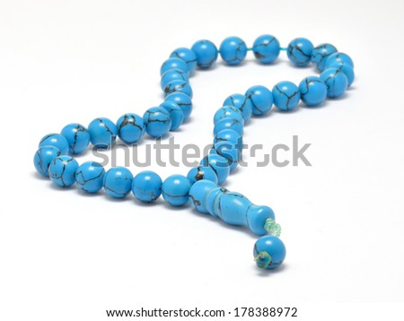 Turquoise Islamic prayer beads isolated on white under studio lighting - stock photo