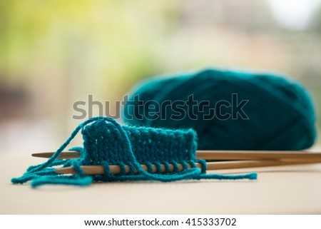 Turquoise knitting wool and knitting needles - stock photo
