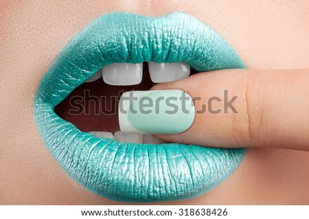 Turquoise lip gloss and a beautiful nails. - stock photo