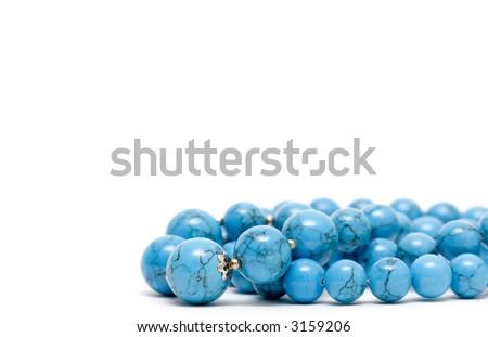 Turquoise mardi gras beads isolated on white - stock photo