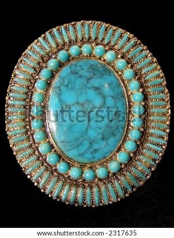 Turquoise medallion on black background - stock photo