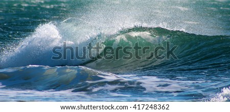 Turquoise ocean wave , shore break