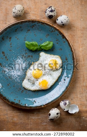 Turquoise plate with fried quail eggs, view from above - stock photo