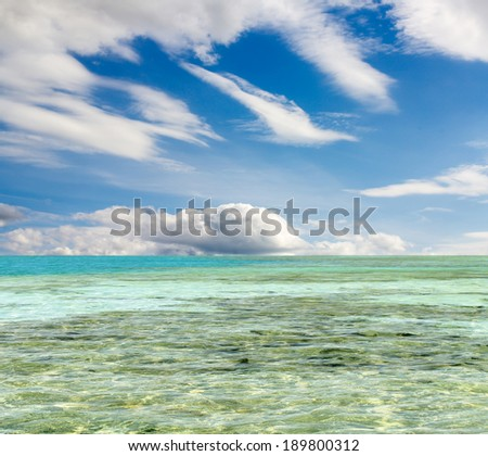 turquoise sea against the sky with clouds - stock photo