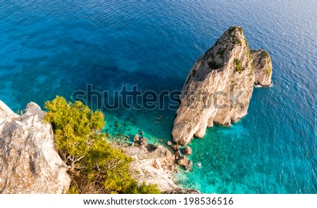 Turquoise sea and a seaside cliff - stock photo