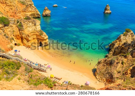 Turquoise sea water at Camilo beach with rock cliffs, Algarve region, Portugal - stock photo