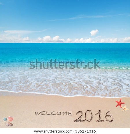 """turquoise water and golden sand with shells and sea stars with """"welcome 2016"""" written on it - stock photo"""