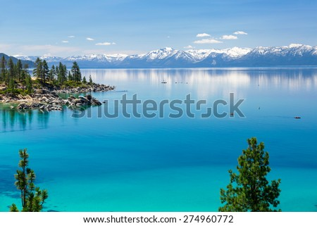 Turquoise waters of Lake Tahoe with view on Sierra Nevada snowy mountains. There are two kayaks on the right side of the photograph. - stock photo