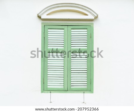 turquoise window in a white wall - stock photo