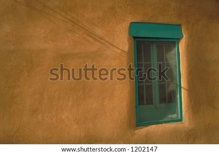 turquoise window on adobe building - stock photo