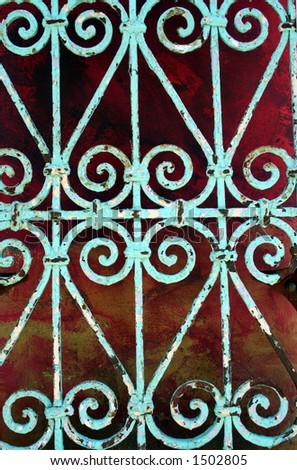 Turquoise Wrought Iron Against Painted WAll - stock photo