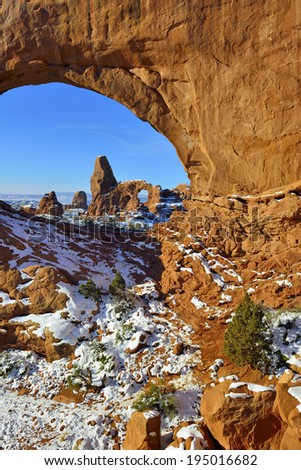 Turret Arch seen through North Window Arch in Arches National Park, Utah in winter - stock photo