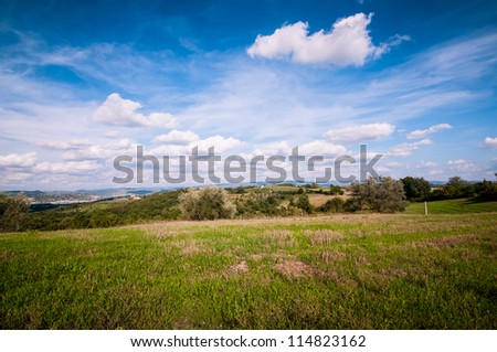 Tuscan countryside landscape with blue sky, clouds and meadows