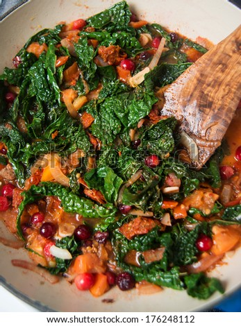 Tuscan Kale Wilted with Tomatoes, Cranberries and Garlic for Healthy Side  - stock photo