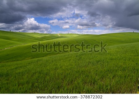 Tuscan landscape Siena hills with cloudy sky - stock photo