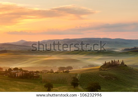 Tuscan villa in the fog on a misty sunrise morning in San Quirico d'Orcia - stock photo