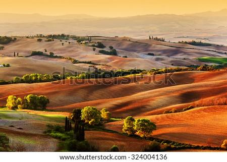Tuscany countryside landscape at sunrise, Italy. Hilly fields, wavy terrain - stock photo