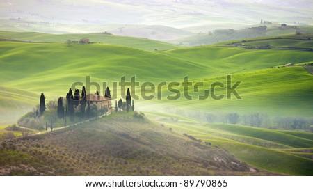 Tuscany farmhouse on hill - stock photo