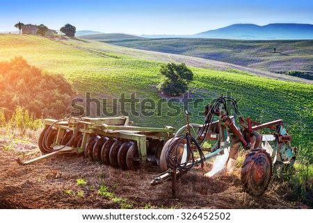 Tuscany landscape at sunrise. Retro, old agriculture machines on Tuscan hills. Italy - stock photo