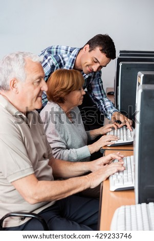 Tutor Helping Senior Woman In Using Computer - stock photo