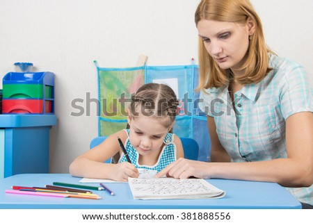 Tutor helps the child to spell the alphabet - stock photo