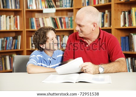 Tutor or father helping a boy with his homework in the library. - stock photo