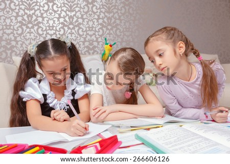 Tutoring each other. Three pretty schoolgirls writing home tasks in exercise books sitting at home - stock photo