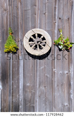 tutsan and raspberry herbs  bunches and old wheel on wooden  wall - stock photo