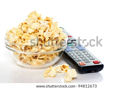 tv remote control and bowl with popcorn on white background. tv watching concept - stock photo
