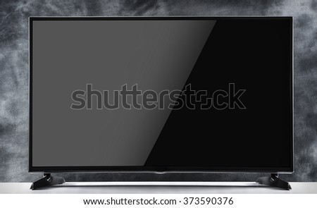 Tv set in a room with dark background - stock photo