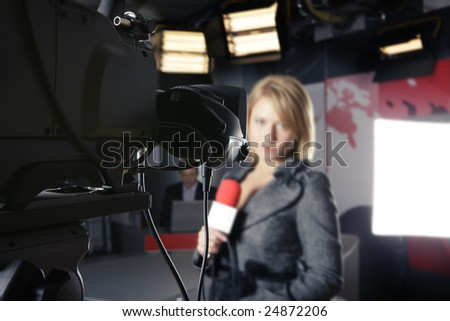 TV studio with close up on a video camera and an unrecognizable woman presenter in the background - stock photo