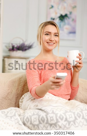 TV time. Young pleasant woman is drinking tea and using remote control to switch channels on the TV. - stock photo