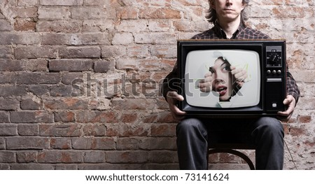 TV with a picture of the girl -facing through a hole in the hands of a seated man . - stock photo