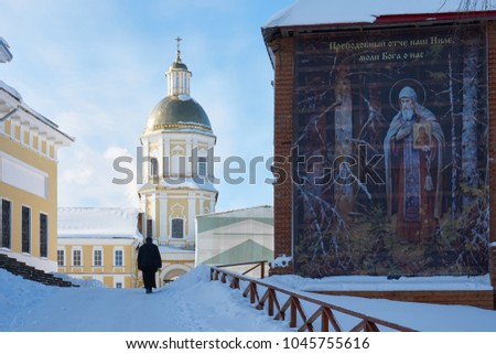 Tver oblast, Russia - February 25, 2018: Monk walks up in the monastery of the Nilo-Stolobenskaya Pustyn, Tver oblast, Russia. Russian text on the wall: Reverend Father our Nile, pray to God for us.