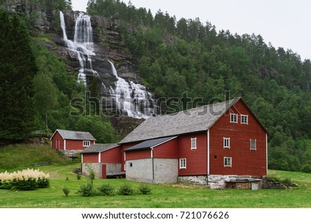 Tvindefossen is a waterfall near Voss, Norway. Traditional Scandinavian wooden house in red color