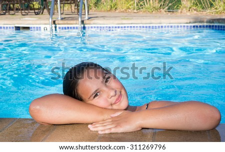 Tween girl in a pool peeking over the edge looking right at the camera with big eyes - stock photo