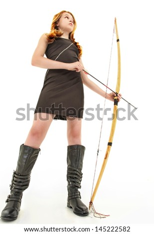 Tween girl in black dress and boots holding a handmade bow and arrow over white background. - stock photo