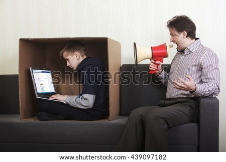 Tween son sitting in a cardboard box with a laptop while his father yells at him through a megaphone - stock photo