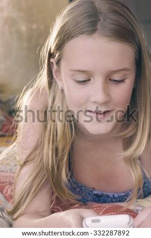 tween with phone in her bedroom - stock photo