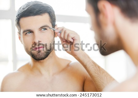 Tweezing his eyebrows. Handsome young man tweezing his eyebrows and looking at himself while standing in front of the mirror - stock photo