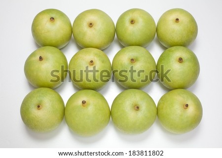 Twelve green apples arranged neatly in three rows. - stock photo