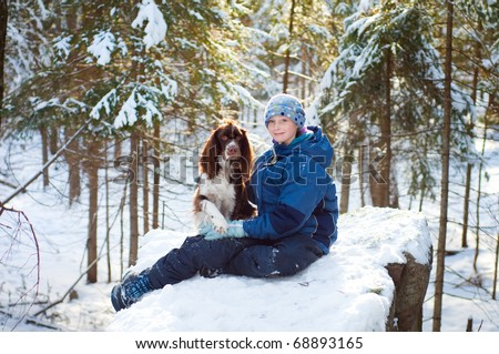 twelve year old girl outdoors in winter with her pet dog