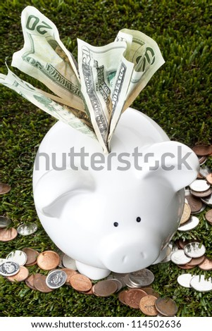 Twenty dollar bill inserted into the piggy bank indicating excess income should be saved - stock photo
