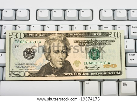 Twenty dollar bill sitting on grey keyboard, spending money online - stock photo