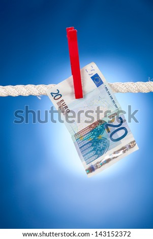 Twenty euro note hanging on white rope against blue background. Money laundering concept - stock photo