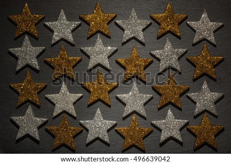 Twenty four silver and golden stars in a row on dark black slate rock background texture.