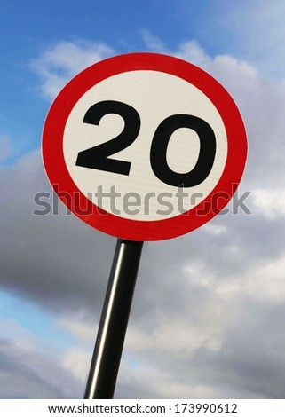 Twenty miles per hour speed limit sign against a partly cloudy sky. - stock photo