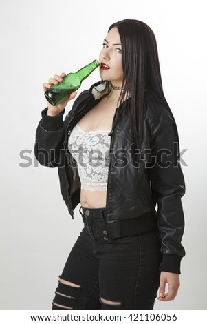 twenty something girl wearing a sexy lace top under a coat, drinking from a green bottle of beer