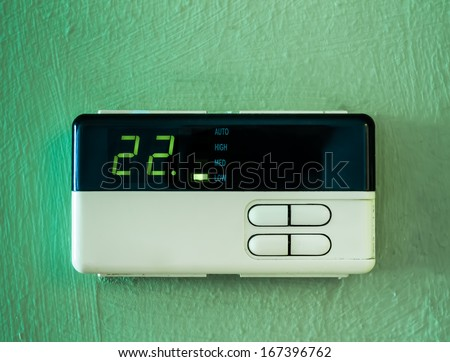 twenty two  celsius heating and cooling air conditioning display on green wall - stock photo