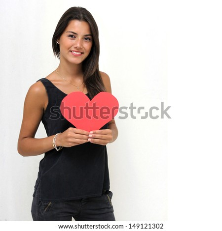Twenty year old woman holding a heart shaped cutout - stock photo